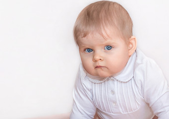 Beautiful girl with blue eyes in white dress stands on all fours on the floor and seriously looking at the camera. Portrait of a baby in 9 months