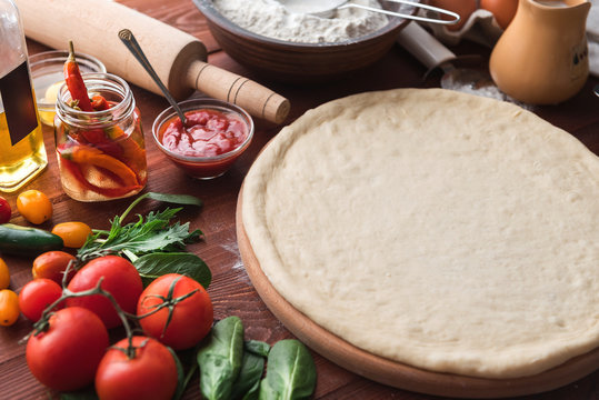 Step-by-step boss makes a pizza margarita. Dough and pizza ingredients