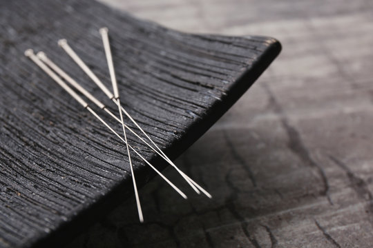 Needles for acupuncture and special stand on grey background, closeup