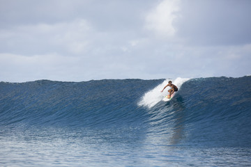 Surfer riding large scale wave, Tahiti, South Pacific
