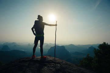 silhouette of woman backpacker hiking on sunrise mountain top