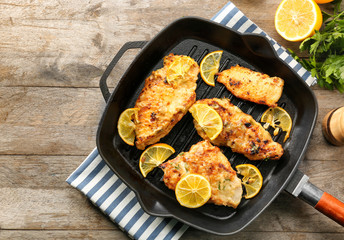 Frying pan with tasty chicken piccata on wooden table
