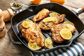 Frying pan with tasty Italian chicken piccata on table