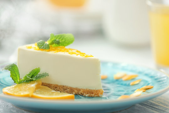 Tasty cheesecake slice with lemons on plate