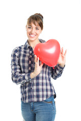 Beautiful young brunette woman playing with red heart shape balloon isolated on white background