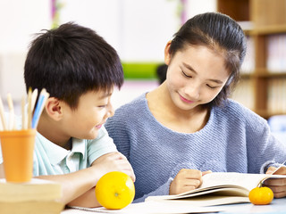 asian elementary schoolgirl and school boy studying together