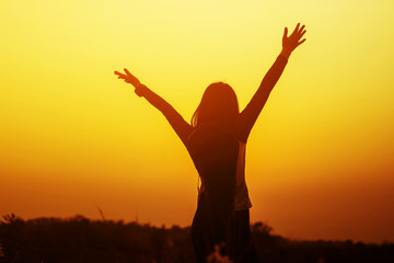 Happy woman raised hands up on the sky at sunset
