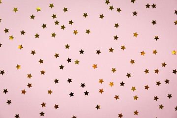 Golden star sprinkles on pink. Festive holiday background. Celebration concept
