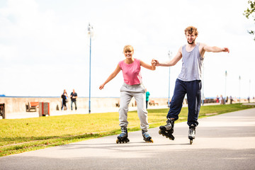 Active people friends rollerskating outdoor.
