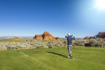 Foto op Plexiglas Golf Rear view of a man playing golf on a Sunny day on a beautiful desert golf course in the Southwestern United states.