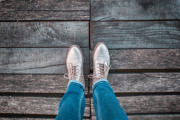 Top view of woman in jeans with shoes standing on the aged wooden floor. Personal perspective used.