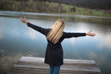 Blonde long hair woman with stretched arms enjoying life. Freedom and happiness concept.