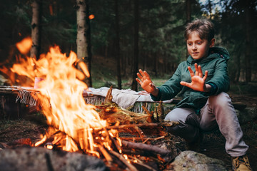 Boy warms his hands near campfire in forest
