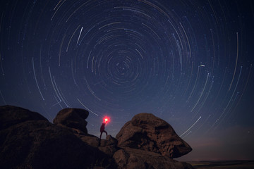 Rock and man silhouette over star tracks
