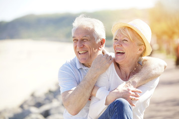 Senior couple relaxing by the sea on sunny day
