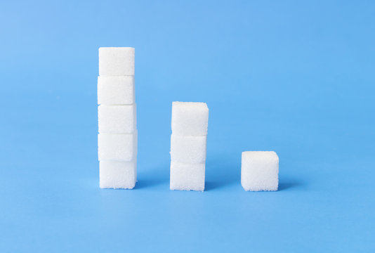 High to low stacks of sugar cubes with blue background, health care concept