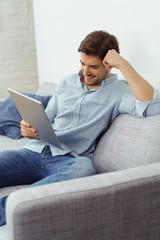 mann liest zuhause am tablet