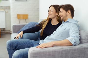 entspanntes paar sitzt auf dem sofa und schaut fern