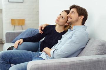 junges paar sitzt auf dem sofa und schaut verträumt nach oben