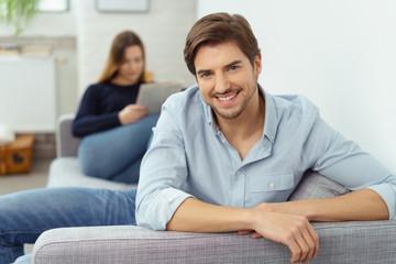 lächelnder mann sitzt zuhause auf dem sofa mit seiner freundin im hintergrund