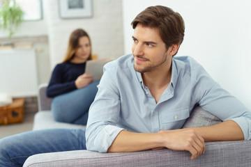 attraktiver mann sitzt entspannt zuhause auf der couch