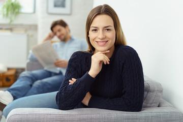 lächelnde frau sitzt auf dem sofa mit ihrem mann im hintergrund
