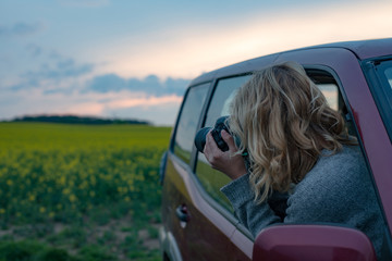 Young woman taking photos while sitting in a car. Female capturing a perfect road trip moment.
