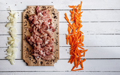 On this photo cutting meat lying with vegetables on wood desk.