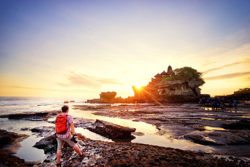 Travel and photography. Young man with camera taking picture of beautiful balinese landscape. Ancient hinduism temple Tanah lot on the rock against sunset sky. Bali Island, Indonesia.