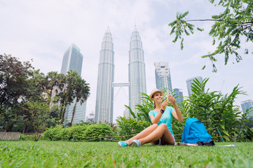 Poster de jardin Kuala Lumpur Travel concept. Pretty young woman in hat using smartphone while sitting on the grass against Petrones Twins Tower in Kuala-Lumpur.