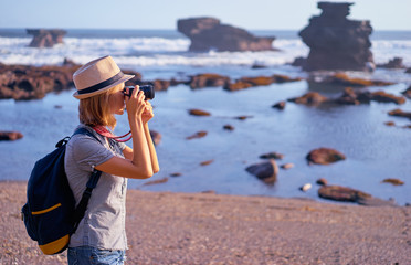 Traveler and photographer. Pretty young woman taking photo on beautiful ocean beach.