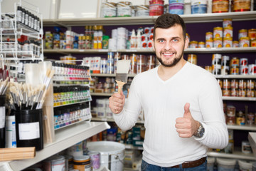 positive male customer examining various types of brushes in paint store