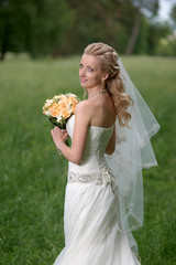 Portrait of Beautiful bride holding bouquet and looking at the camera