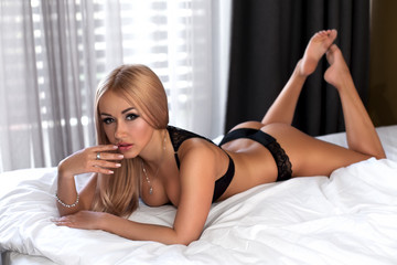 Beautiful blonde model posing at the bed
