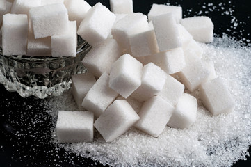 white granulated sugar and refined sugar on black tables surface, closeup