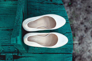 bride's biege shoes on heel on a wooden board tiffany colour