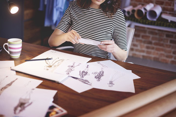 Fashion designer photographing sketches with phone