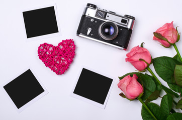 Old vintage photo camera and pink roses on a white background.