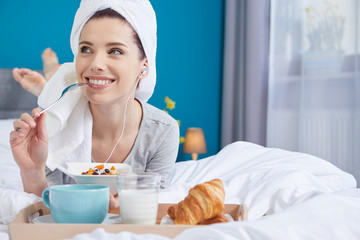 Portrait of a happy smiling european woman eating a healthy breakfast of fruit and yoghurt in bed.