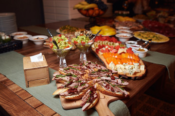 Unformal fourchette table with small bruschettas, guacamole and sliced vegetables