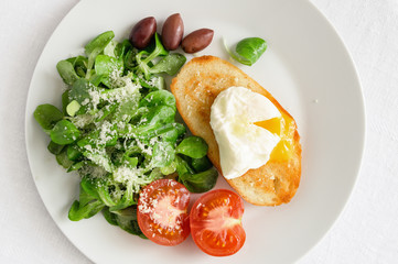 corn salad dressed with olive oil and lemon juice sprinkled with parmesan,  poached egg toast, fresh tomato, and kalamata olives