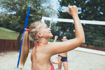 Group of young people playing beach volleyball on beautiful sunny day. Woman holding water bottle.