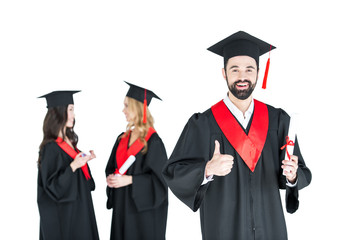 Happy young man in academic cap holding diploma and showing thumb up
