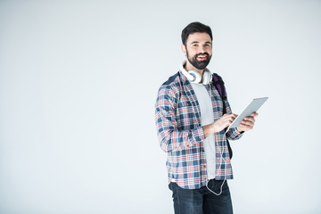 bearded man with headphones and digital tablet on white with copy space