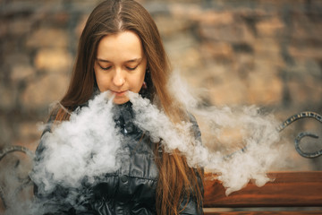 Vape. A young beautiful white girl is sitting on a vintage bench and is smoking an electronic cigarette. Lifestyle.