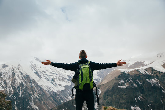 Young man with backpack standing with raised hands on top of a mountain