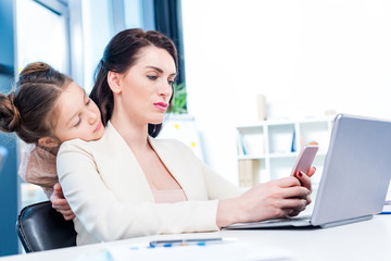 attractive businesswoman working with little adorable daughter in office