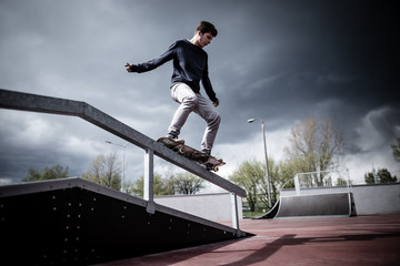 Skater doing 50-50 trick on rail in skatepark during stormy dramatic weather