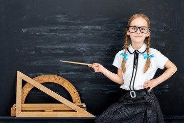 Little girl against blackboard. School concept