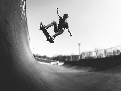 Skateboarder doing ollie on ramp -  black and white